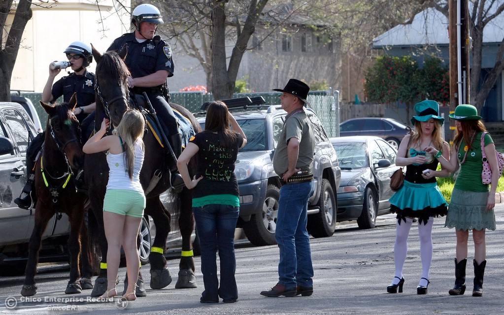 . Partiers walk past mounted patrol units Det. Abigail Madden and Sgt. Scott Ruppel along Ivy St. near W. 4th St. as St. Patrick Day celebrations spill into the streets as partiers, CSUC/Butte students and non-students, enjoy the week off on Wednesday, March 17, 2010 in Downtown Chico, Calif. 