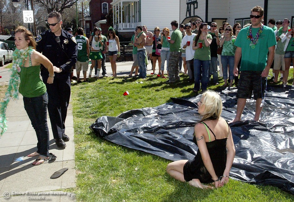 . Monday March 17, 2008 in Chico, CA. Saint Patricks Day. In this picture,outside a party at 2nd and Ivy street Chico two got into a fight on the sidewalk. They were both taken away in handcuffs by law enforcement. Green shirt is Janette Lawson,black shirt is Alison Post.Chico Police officer Andrei Carlisle cuffs them.(Ty Barbour/Chico Enterprise-Record)