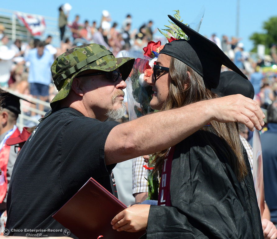 . Larry Hayden gives his daughter Lauren Schnelli a hug, a kiss and a flower bouquet after the women\'s track and field star graduated Saturday, May 20, 2017, at University Stadium in Chico, California.  (Dan Reidel -- Enterprise-Record)