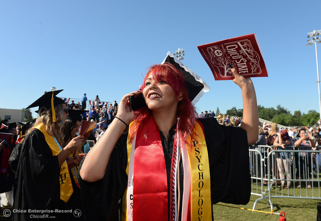 . Anaiza Novoa looks for family in the crowd as she speaks to them by phone just before Chico State graduates receive their diplomas Saturday, May 20, 2017, at University Stadium in Chico, California.  (Dan Reidel -- Enterprise-Record)