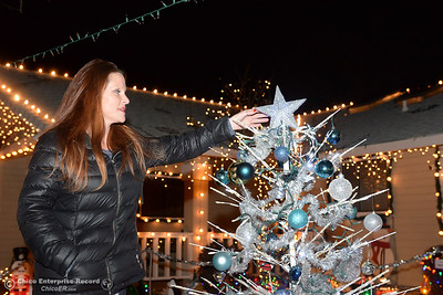 Kari Tiffany adjust the star at the top of the Christmas tree in the middle of her family's light display Wednesday, Dec. 12, 2018, at the Tiffany home on the 500 block of Cimarron Drive. The tree has ornaments given to the family by children who recieved wishes from  Make-A-Wish, for which the Tiffanys collect donations every holiday season. (Dan Reidel -- Enterprise-Record)
