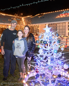 Left to right, Tim, Ellie and Kari Tiffany pose in front of a train from the collection of the late Don Corrie in their Christmas light display Wednesday, Dec. 12, 2018. their home on the 500 block of Cimarron Drive is one of many on the 2018 Chico Tour of Lights in Chico, California. (Dan Reidel -- Enterprise-Record)
