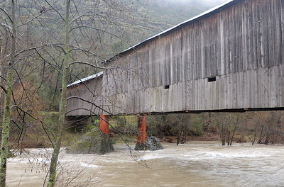 Fast moving muddy water flows beneath the Honey Run Covered Bridge in Butte Creek Canyon as the storm continues to roll through Butte County in northern Calif. Tues. Jan. 10, 2017. (Bill Husa -- Enterprise-Record)