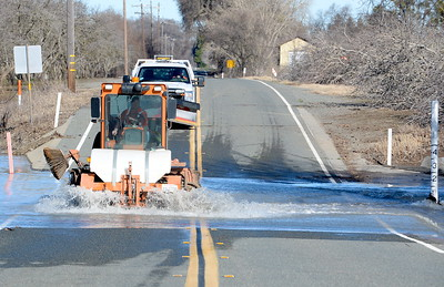 A sweeper drives through a previously flooded section along River Road in Chico, Calif. Friday. River Road remains closed between Ord Ferry Rd. and W. Sacramento Ave. Friday. Some Chico area roads re-opening after flooding during the storm last week. Friday, Jan. 13, 2017. (Bill Husa -- Enterprise-Record)