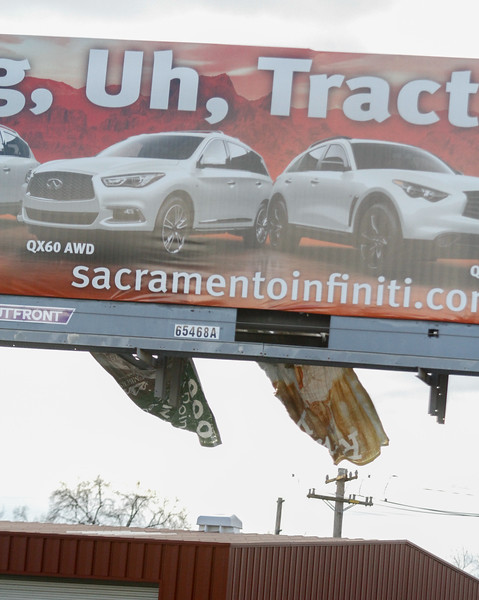 A torn billboard flaps in the wind across from Fix Auto, formerly Chico Collision Center as owner Mark Page talks about his new digital sign Wednesday January 11, 2017 in Chico, California. Digital signs are not addressed in the cities code so the city is deciding if they should make an ordinance for them. (Emily Bertolino -- Enterprise-Record)