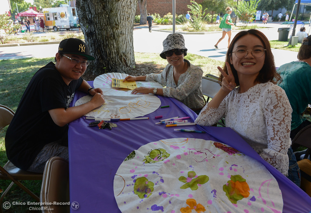 ". Jiayu Yang and her friends make ""Crazy Hats,\"" at an art booth during the Chico World Music Festival Saturday September 9, 2017 at CSUC in Chico, California. (Emily Bertolino -- Enterprise-Record)"