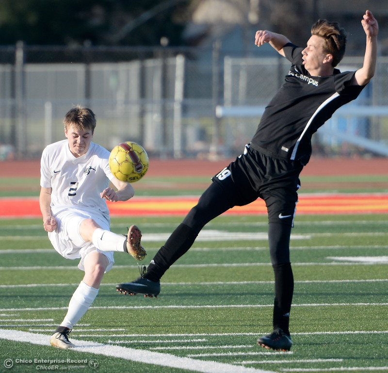 . Chico #2 Trevor Silverman kicks one upfield under pressure by West Campus #19 Nic Cordero during the first round of the NorCal state playoffs Chico High vs West Campus boys soccer at Chico, Tues. March 6, 2018. (Bill Husa -- Enterprise-Record)
