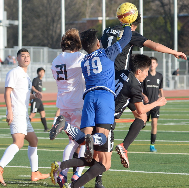 . Chico #21 battles for a header near the West Campus goalie Brian Sanchez during the first round of the NorCal state playoffs Chico High vs West Campus boys soccer at Chico, Tues. March 6, 2018. (Bill Husa -- Enterprise-Record)