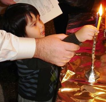 A father guides the hand of his 3 year old son to light the first candle during Channukah at a Family Candle Lighting at Temple Beth Am, Seattle, Washington