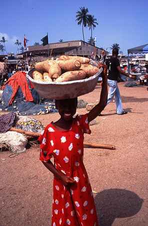 "This young girl was carrying kasava which would probably be used to make ""fufu"". a Ghanaian staple.  It would be grounded with a large heavy mallet and made into a paste, then shaped into an oval, and eventually dipped in a sauce or ""soup"".  Since this photo was taken near a market, the girl had either just bought them or was going to sell them.  The location is Elmina, the sight of Elmina Slave Castle, now a World Heritage Site.  We were in Elmina as a part of our service as volunteers with ProLink, an NGO working on HIV/AIDS prention programs."