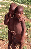 These Himba childrren are at peace in their world and live a gently and violence free life in their village.