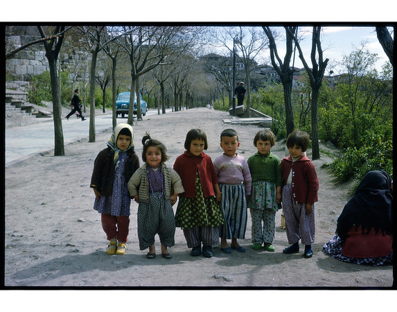This photo was taken by the photographer, Peter Schnurman, in 1961 in Ankara, Turkey, in Ulus, a poor section of the city.  Note that the women on the right would not permit her photo to be taken but did permit hr childrren to be photographed.  This photo was taken with Kodachrome II, ASA 25.