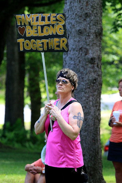 "Community members in Lunenburg held a ""Children Belong Together"" at the gazebo in town on Saturday. Holding a sign at the event is Tammy Cisneros of Gardner. SENTINEL & ENTERPRISE/JOHN LOVE"