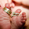 Photo of wedding rings on babies toes