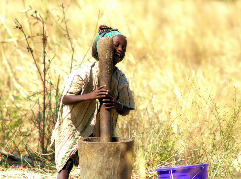 """My personal favourite of my photographs. I was in the village overnight adn this was taken early next morning. Few knew I ws still there, and she was working hard at her chore. But as she saw me she started to laugh adn eventually could not continue as she was in fits of laughter. Even in extreme poverty there is lighter times of fun.<br /> <br /> *+ALL MONEY RAISED FROM SALE OF MY ART, AND DONATIONS MADE VIA OUR CHARITY WEBSITE, GOES TO HELP THESE PRECIOUS CHILDREN. WE TAKE NOTHING OUT OF WHAT YOU GIVE TOWARDS CHARITY OVERHEADS. WE ARE NOT SALARIED AND COVER OUR OWN TRAVEL EXPENSES. SO ALL THAT YOU GIVE GOES TO THESE CHILDREN+*<br /> <br /> To make a donation, or find out more, Please visit our Charity Mission website: *""""http://www.philadelphia33.org/*"""" <a href=""""http://www.philadelphia33.org/"""">http://www.philadelphia33.org/</a><br /> <br /> See more of my work at :<br /> *""""http://www.redbubble.com/people/joshuatree1*"""" <a href=""""http://www.redbubble.com/people/joshuatree1"""">http://www.redbubble.com/people/joshuatree1</a>"""