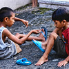 Two boys playing with live spiders fighting on a stick. Seen at Malabon, Philippines.