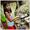 A young girl helping her mother barbecue banana fritters. Taken in Loboc River, Bohol, Philippines.
