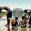 Children from poor families, take their showers on a plaza beside a public fountain. Seen at the plaza at the foot of Del Pan Bridge, Manila, Philippines.