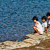 Children are already playing by the seawall even before breakfast. Photo taken in Calayo Village, Batangas, Philippines.