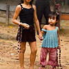 Big sister and small sister selling trinkets alng a dirt road in a small village at Rio Negro, Amazon River, Brazil.