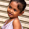 A very young girl too shy to smile because she is missing two front teeth. Taken in the financial district of Singapore.