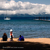 It is early spring and still cold but this boy with his brother and mother are bundled up and enjoying the shore at South Lake Tahoe, California, USA.