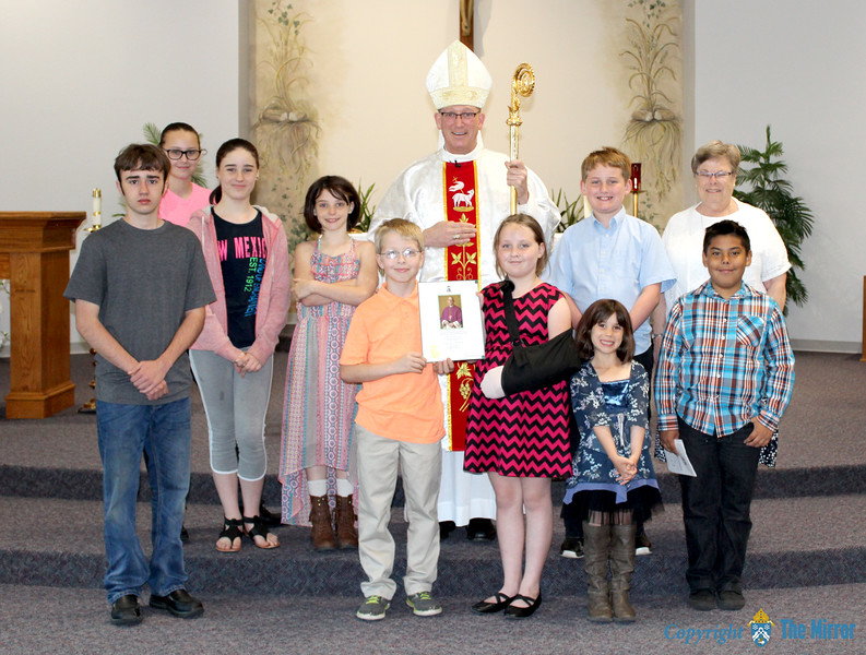 PARISH SCHOOL OF RELIGION—Bishop Edward M. Rice visited Our Lady of the Ozarks Parish School of Religion (PSR) on Sun., May 13, to congratulate them on their participation in the 2018 Lenten Challenge. They are pictured with Sr. Charlotte Flarlong, SSND. These nine students won the PSR category for most funds raised and also presented Bishop Rice with the winning name suggestion for the tiny home in Eden Village: Our Lady's Cottage. (<i>The Mirror</i>)