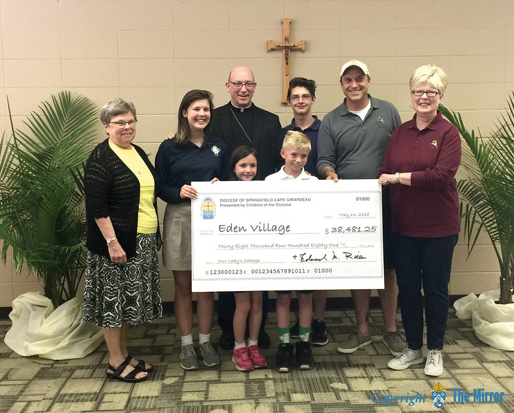 "WORK OF MERCY—Representing all the children of the Diocese of Springfield-Cape Girardeau, Bp. Edward M. Rice and four students from St. Agnes Catholic School, Springfield, presented a check May 14 in excess of $38,000 to Linda Brown, Eden Village co-founder, and Nate Schlueter, Eden Village Chief Operating Officer. As their Lenten project, the youth of the diocese raised money to build one ""micro-home"" in Eden Village for a chronically disabled homeless individual. (Photo by Kim Brayman/<i>The Mirror</i>)"