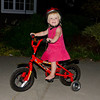 Ava sitting on a bike in the front-yard.