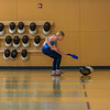 """Hannah playing a training game at fencing class.  Four kids would play at a time.  Each kid had a face mask in a corner of the playing space that was """"theirs"""".  A set of pins (4?) were set up in the middle.  The goal was to get three pins in your mask.  You could take pins from either the middle or another person's mask, but you could not carry more than one at a time."""