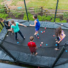 Kids jumping with water balloons on the trampoline at Hannah and Kaitlyn's birthday party