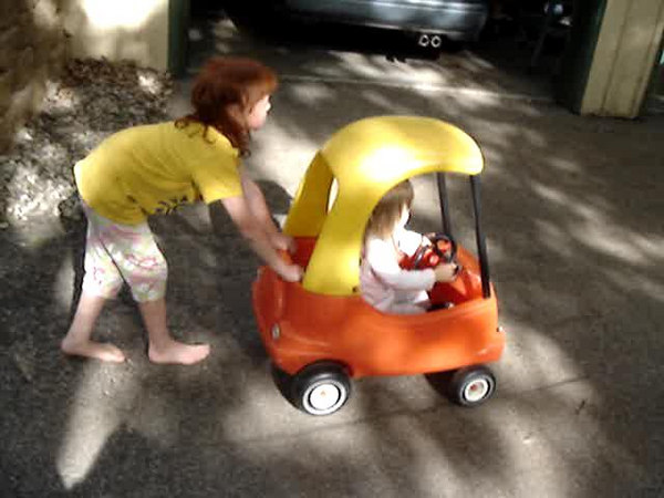 Zina pushes Alice in a toy car
