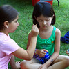 Lorelei Ahn having her face painted by Ani Seppellin at the downtown day in Ashurnham .
