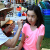 Rachel Ahn having her face painted by Karren Sargent at the downtown day.