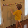 Lining his alphabet letters up on the door.