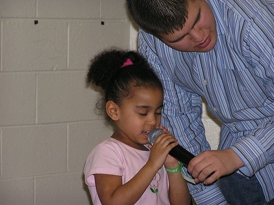 Girl Praying for Offering during Kidz C.L.U.B. while Isaiah Hold the Mic.