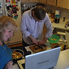 Christopher cutting up the fingerling potatoes with being supervised by Mom + Little Man via Skype