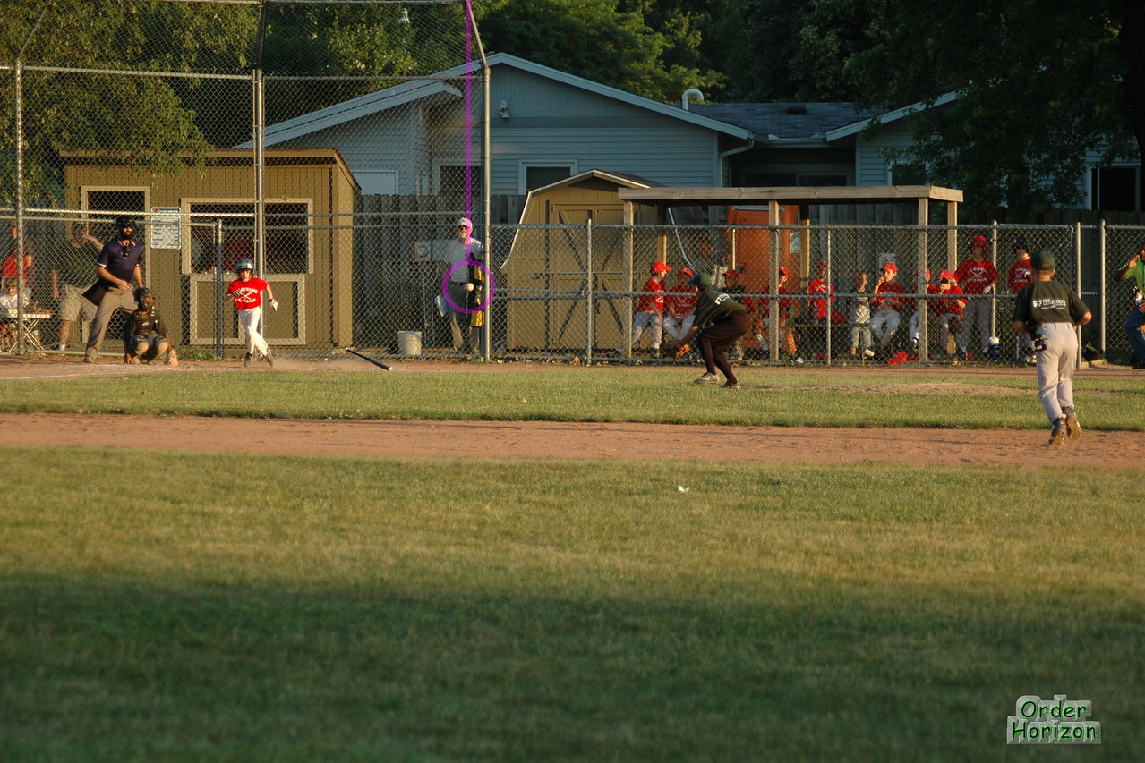 The pitcher catches this hit and throws the runner out at first. The ball is just about to pass in front of the barn.