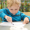Jack Moscinski, 4, of Ashby, focuses during a craft hour at the Ashby Free Public Library during a rainy Wednesday afternoon. SENTINEL & ENTERPRISE / Ashley Green