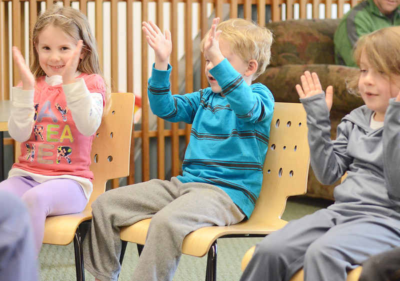 """Ryleigh Pennell, 4, Jack Moscinksi, 4, and Mackenzie O'Connor, 5, all of Ashby, sing and dance to """"The Itsy Bitsy Spider"""" at the Ashby Free Public Library during a rainy Wednesday afternoon. SENTINEL & ENTERPRISE / Ashley Green"""