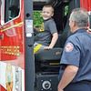 Joshua Agnese, 7, hangs out in the front seat of a fire truck with Lieutenant Greg May during DPW Day on Wednesday afternoon. The event was put on by the Fitchburg Department of Public Works and ACE of Central MA. SENTINEL & ENTERPRISE / Ashley Green