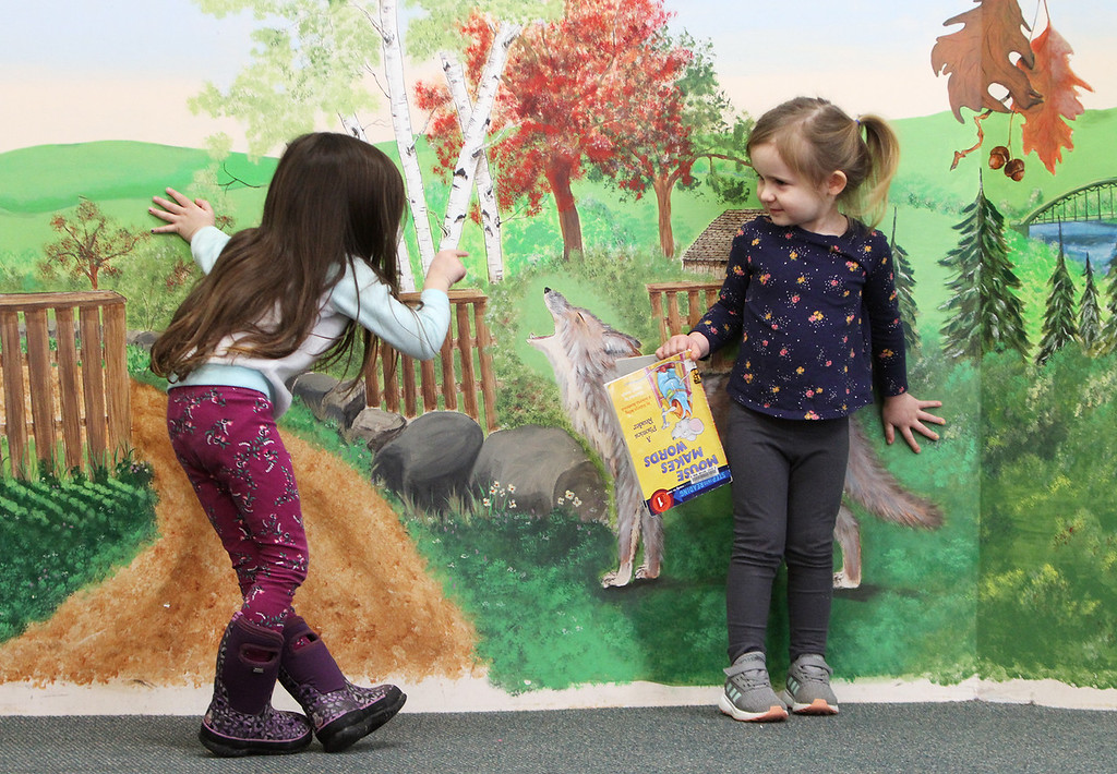 . Dads & Donuts free play time with snacks at Tyngsborough Public Library. Luella Martinez, 3, of Westford, left, and Madison Melville, 4, of Dracut, who\'d just met at the Library, play on the small stage. (SUN/Julia Malakie)