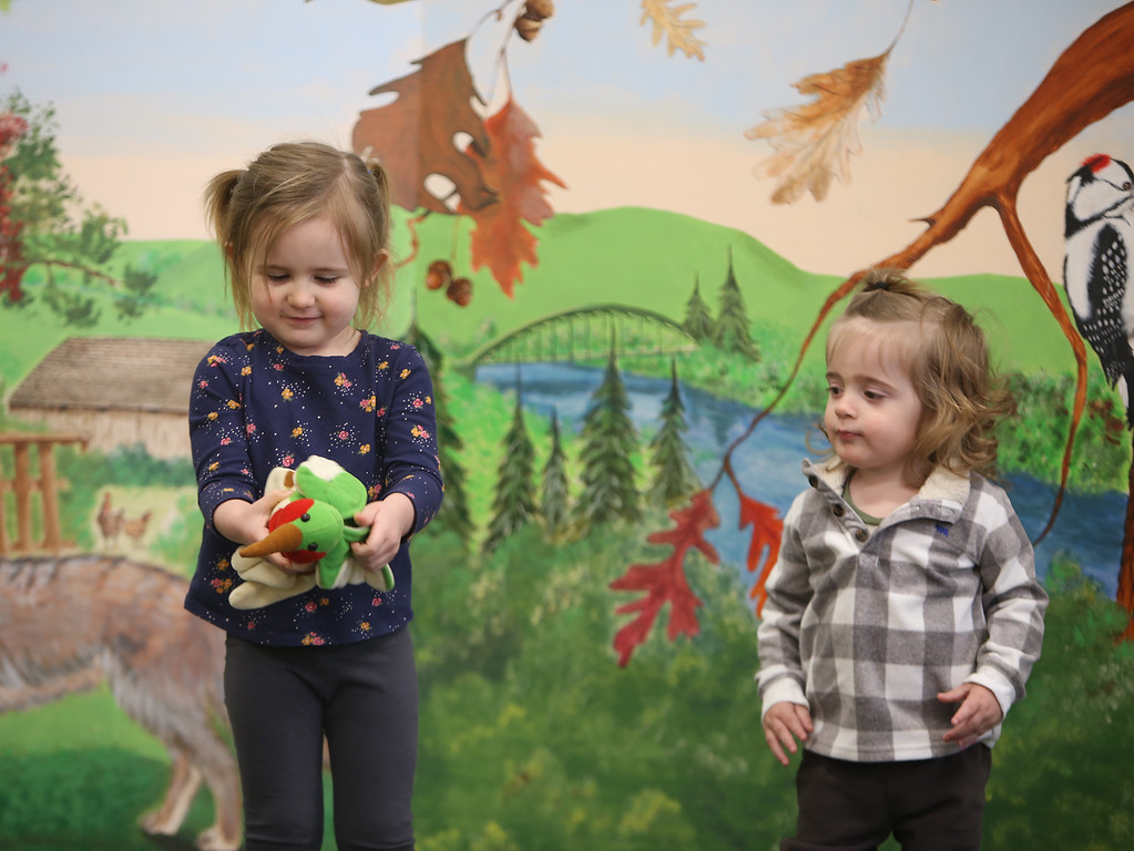 . Dads & Donuts free play time with snacks at Tyngsborough Public Library. LMadison Melville, 4, of Dracut, and Caius Martinez, 20 months, of Westford, who\'d just met at the Library, play with hand puppets on the small stage. (SUN/Julia Malakie)