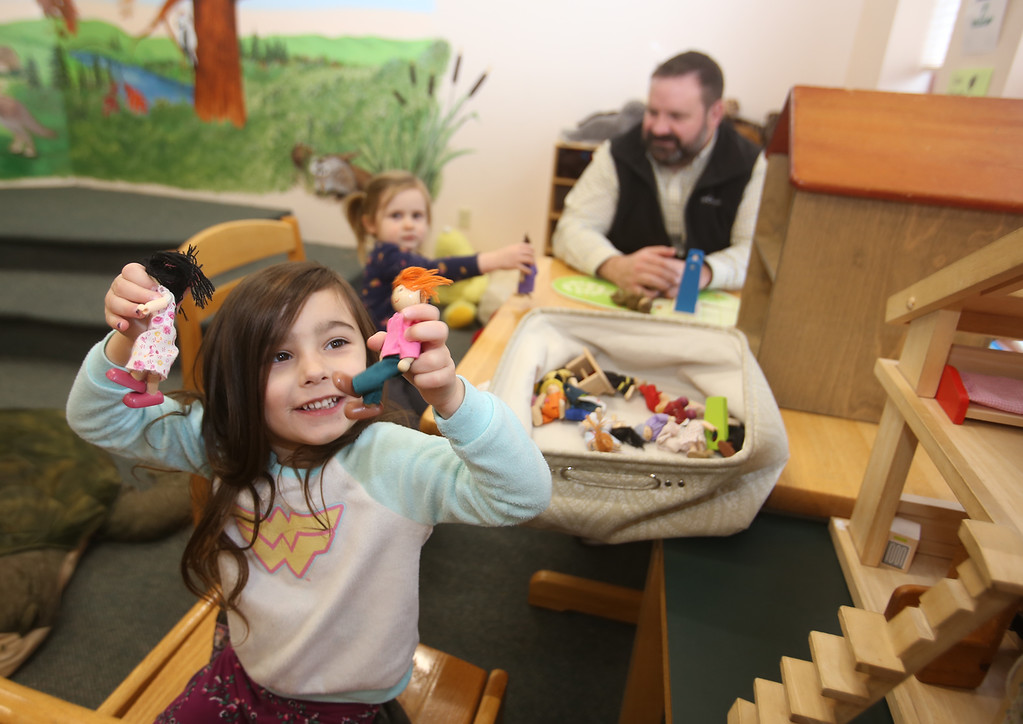 . Dads & Donuts free play time with snacks at Tyngsborough Public Library. Luella Martinez, 3, of Westford, plays with the dolls and doll house. (SUN/Julia Malakie)