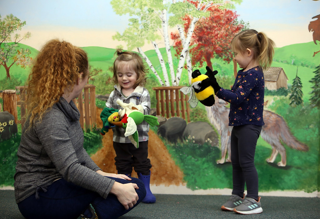 . Dads & Donuts free play time with snacks at Tyngsborough Public Library. Courtney Schmitt of Westford and her son Caius Martinez, 20 months, and Madison Melville, 4, of Dracut, play with hand puppets. (SUN/Julia Malakie)