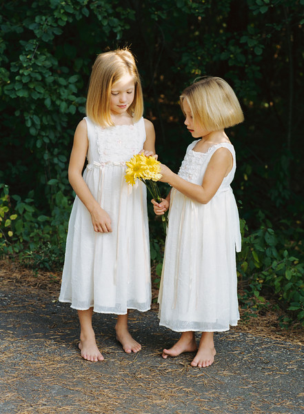 SISTERS IN WHITE  DRESSES SHARING DAISIES_066
