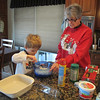 Chase helps Grandma Jean mix the cheese and spices for lasagna.