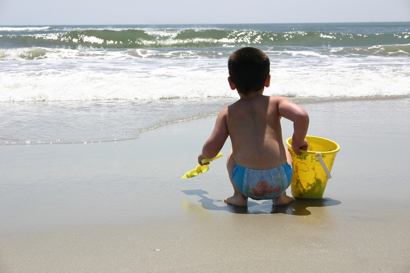 Sam at the beach a few years ago, expecting good things to come right into his bucket. Something swashbuckling about it, Finding Nemo swimmie aside.