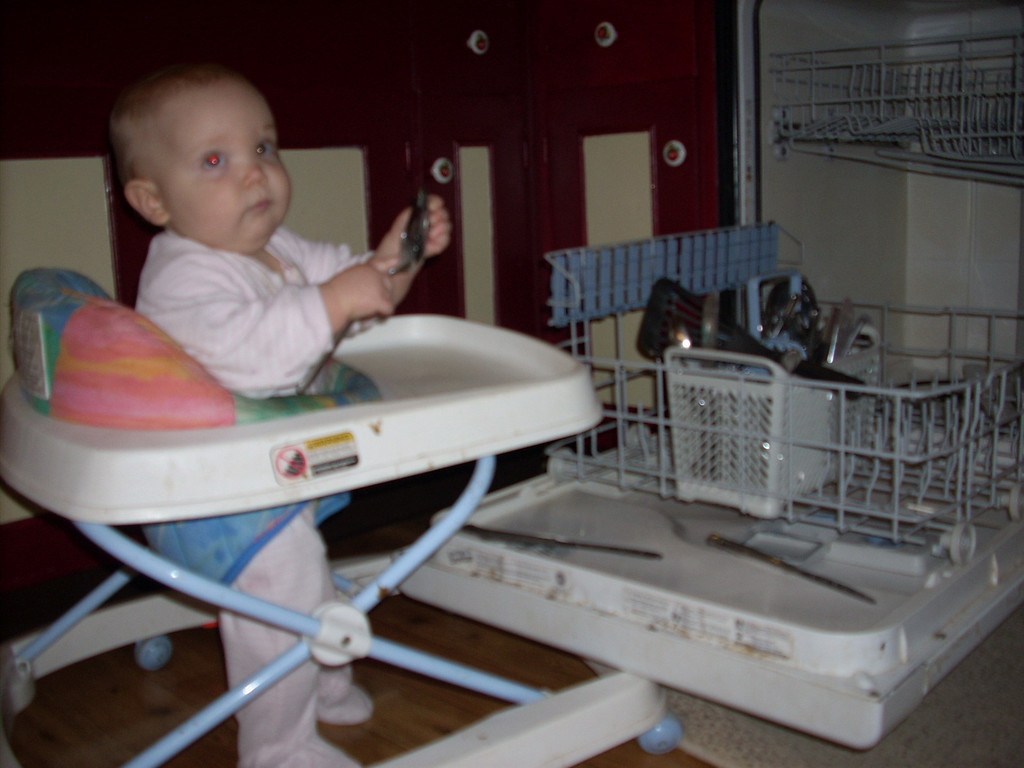 Loves the dish washer!  This was the final days she used her walker. By the 10th month, she refused to go in it. She could get around so much faster crawling.