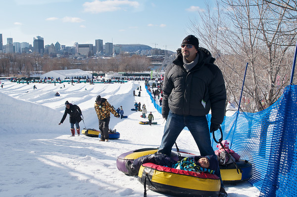 Mikail hauling the kids up the tube sledding hill at the Fête des Neiges - Snow Festival.  Urbanites flock out to enjoy the snow with the beautiful Montreal skyline in the background.